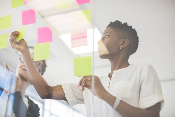 Businesswomen discussing over sticky notes stock photo