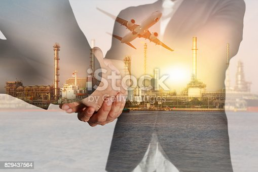 istock businesswomen double handshake, airplane, oil fuel factory plant with sunset 829437564