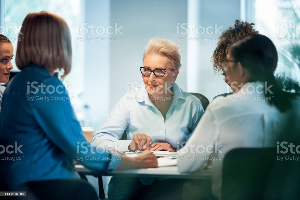 Businesswomen having meeting at desk in office Businesswomen having meeting at desk in office. Senior expertise is advising new plans to colleagues. Female professionals are working on start-up business. 35-39 Years Stock Photo