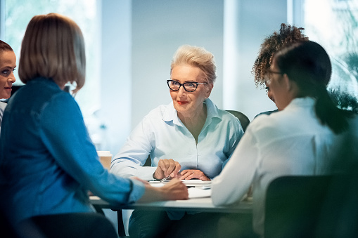 Businesswomen Having Meeting At Desk In Office Stock Photo - Download Image Now