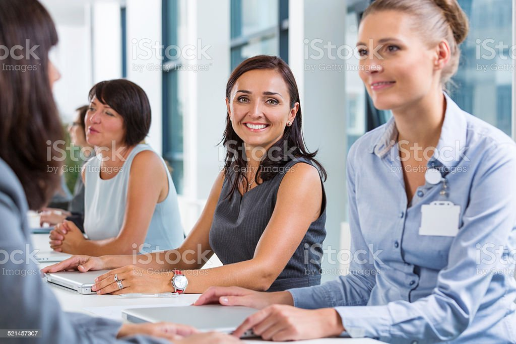 Businesswomen having meeting Group of businesswomen having meeting, working together and discussing. Focus on the cheerful woman smiling at camera. Adult Stock Photo