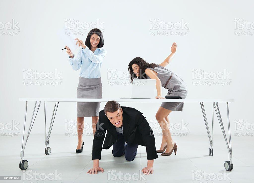 Businesswomen hitting male colleague stock photo