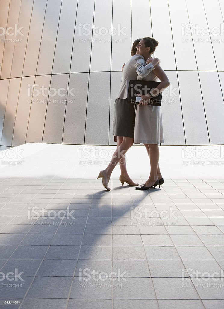 Businesswomen hugging outdoors royalty-free stock photo