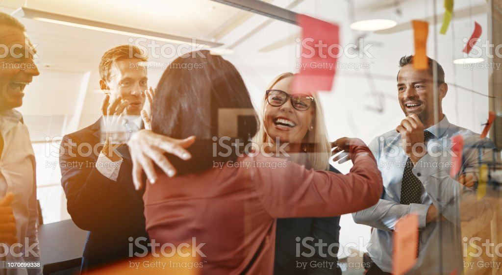 Businesswomen hugging while brainstorming with their team in an office - Royalty-free Abraçar Foto de stock