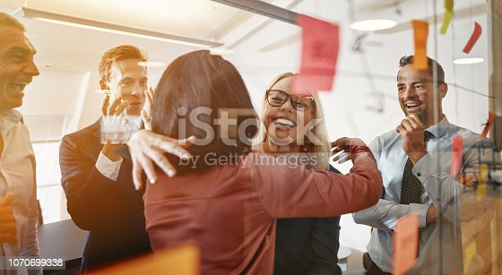 Two smiling young businesswomen hugging while brainstorming with sticky notes on a glass wall with colleagues in a modern office