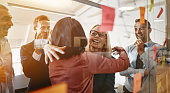 istock Businesswomen hugging while brainstorming with their team in an office 1070699338