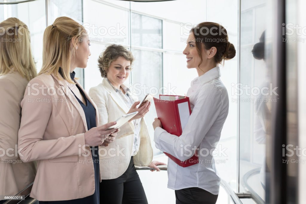 Businesswomen in glass elevator royalty-free stock photo