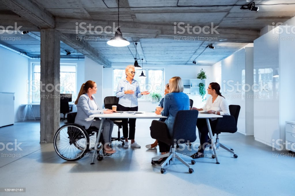 Businesswomen listening to their role model Businesswomen listening to their role model in office. Female executives are planning new business strategies. They are working at desk. 35-39 Years Stock Photo