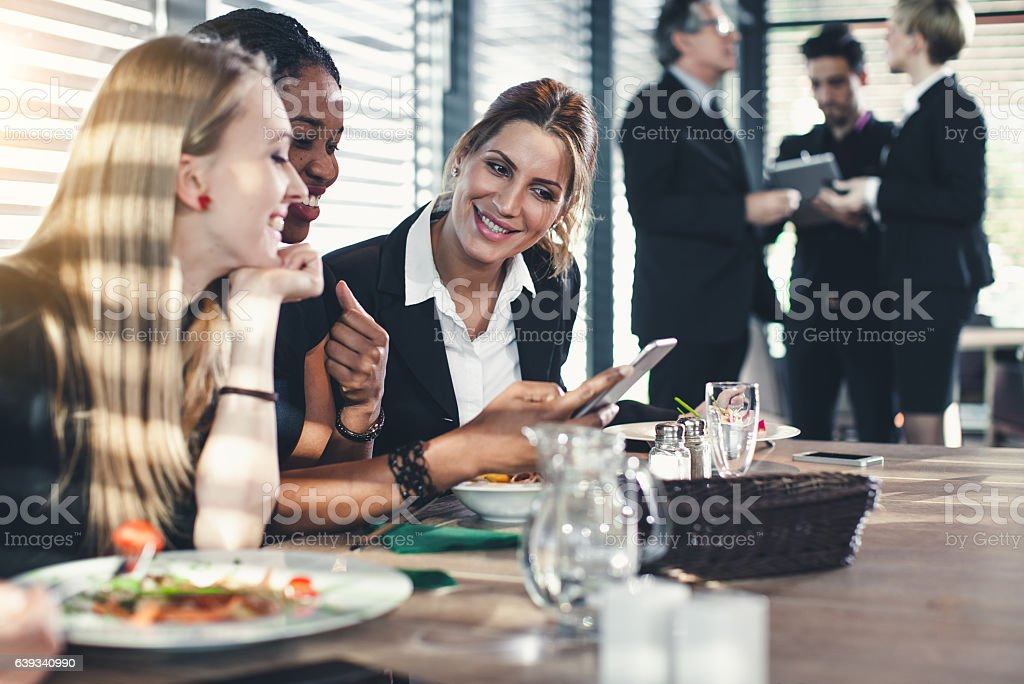 Businesswomen Looking at Smart Phone During Business Lunch and Laughing stock photo