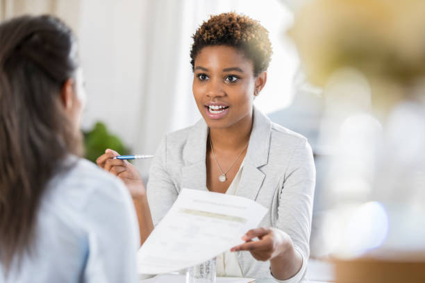 Businesswomen meet to discuss document stock photo