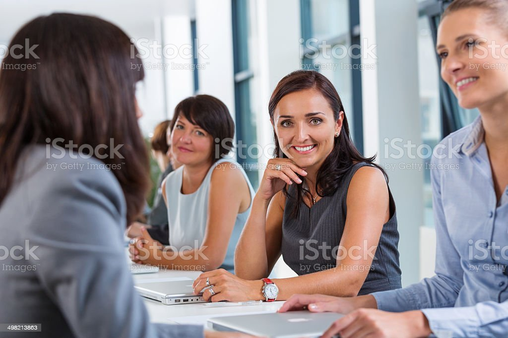 Businesswomen meeting Group of businesswomen having meeting, working together and discussing. Focus on the woman smiling at camera. 30-39 Years Stock Photo