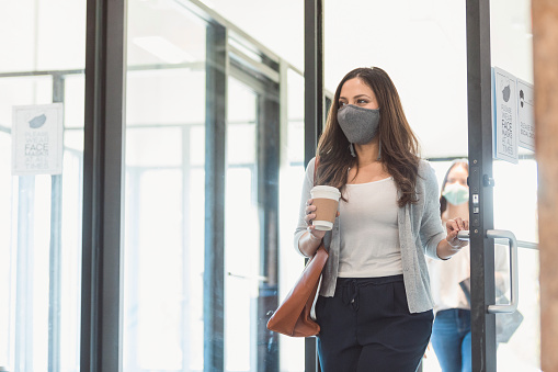 A mid adult businesswoman enters her office during the COVID-19 pandemic. A colleague is walking behind her, practicing the proper social distancing protocol. The businesswomen are wearing protective face masks.