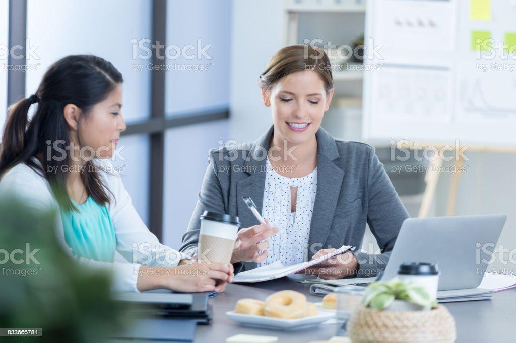 Geschäftsfrauen überprüfen Dokumente während der Frühstücks-Treffen – Foto