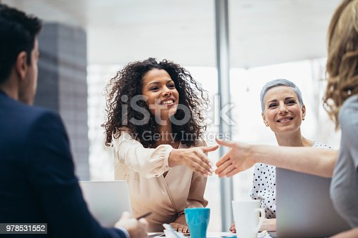 istock Businesswomen shaking hands at the office 978531552