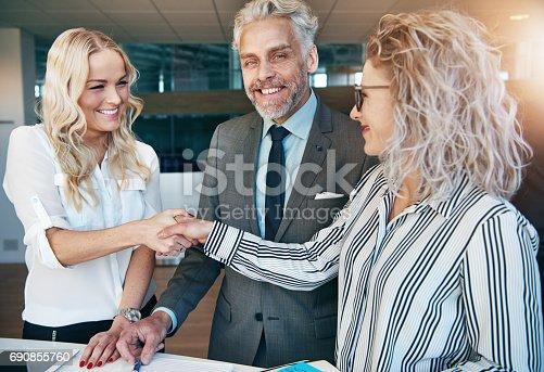 istock Businesswomen shaking hands during meeting in office 690855760