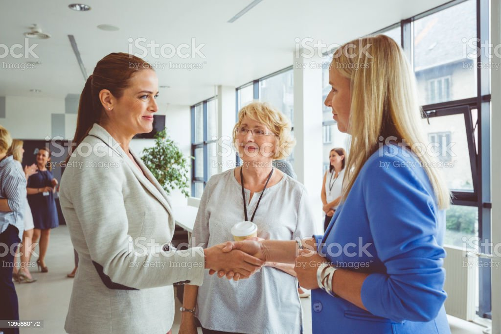 Businesswomen shaking hands during seminar Women meeting and shaking hands during coffee break in a seminar. Group of women meeting and greeting during a conference. Active Seniors Stock Photo