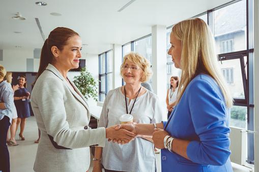 Businesswomen Shaking Hands During Seminar Stock Photo - Download Image Now