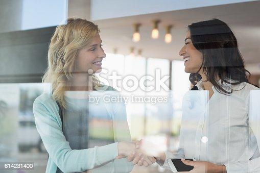 istock Businesswomen shaking hands in office 614231400