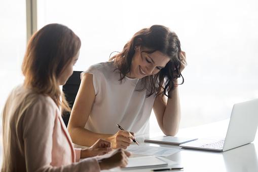 istock Businesswomen sitting at desk analyzing financial report 1092087498