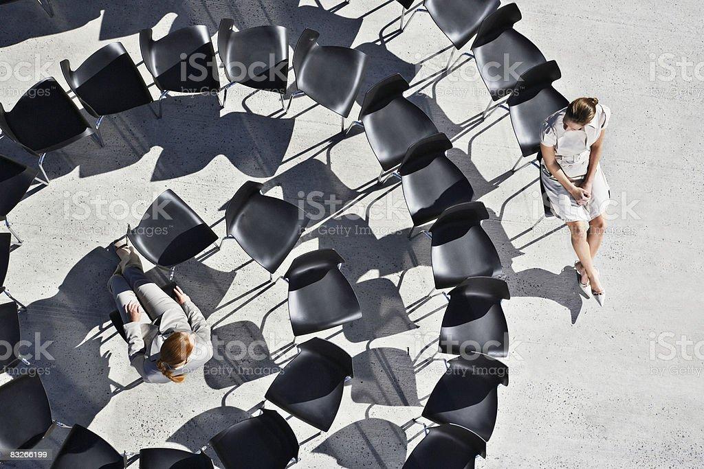 Femmes assis dans la spirale de chaises de bureau photo libre de droits