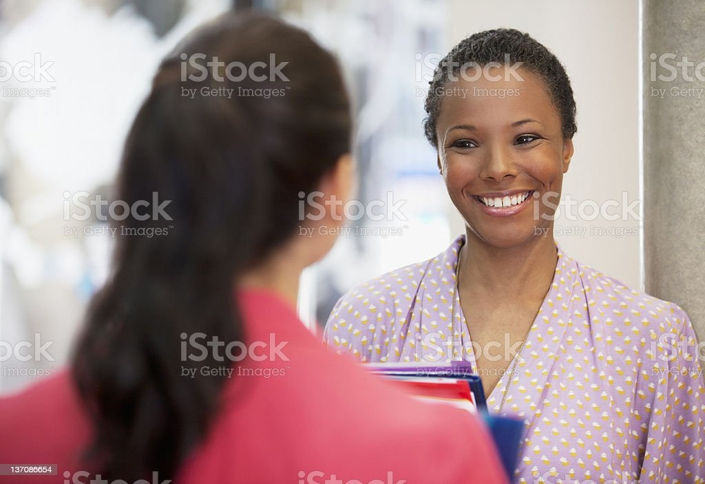 Businesswomen smiling face to face royalty-free stock photo