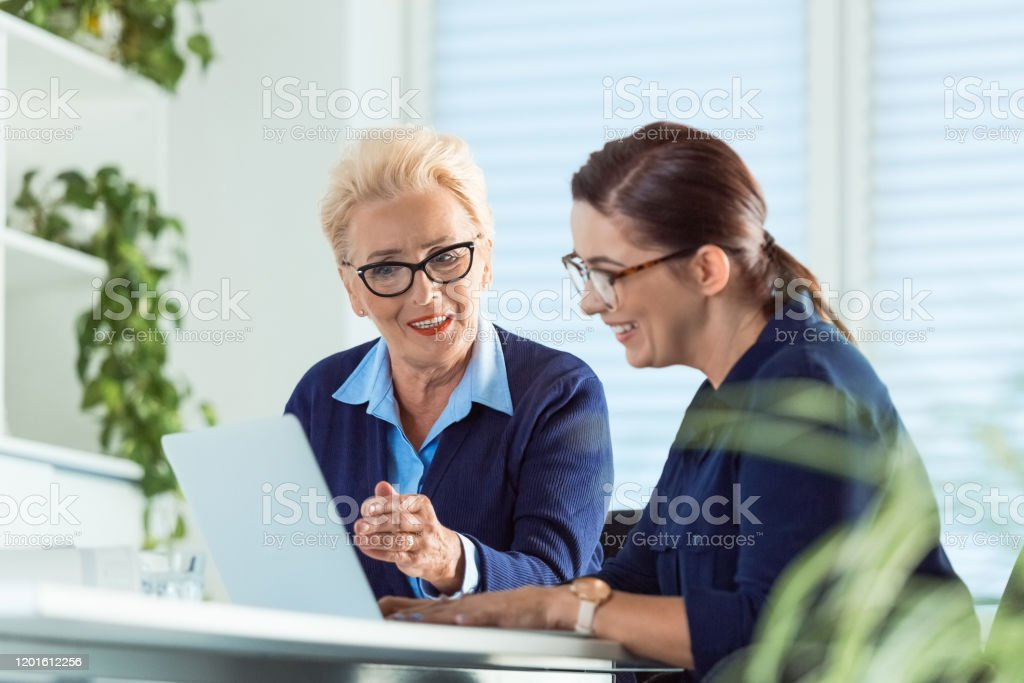 Businesswomen smiling while looking at laptop Businesswomen smiling while looking at laptop. Female executives are working in new business. They are sitting in office. 40-44 Years Stock Photo