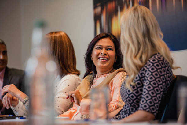 Businesswomen Talking Before a Meeting Two businesswomen talking while sitting down at a conference table. Waiting for the meeting to start. staff meeting stock pictures, royalty-free photos & images