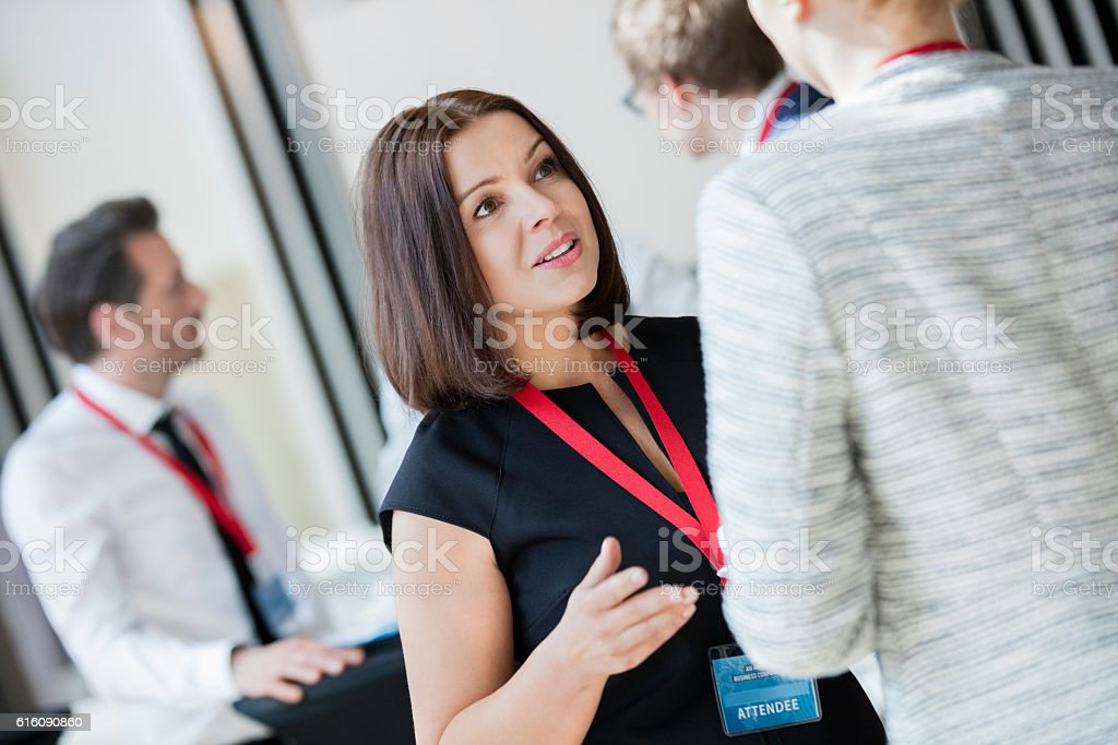 Businesswomen talking during coffee break at convention center stock photo