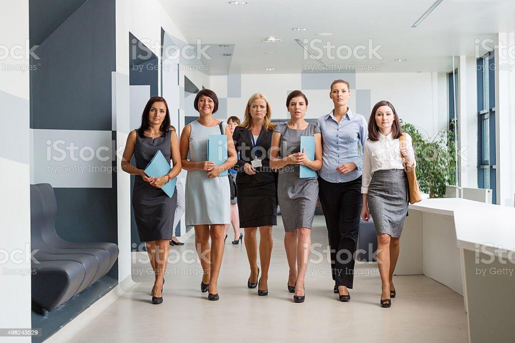 Businesswomen Team Group of confident businesswomen walking down the hall in modern interior. 30-39 Years Stock Photo