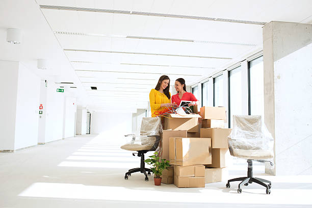 Businesswomen unpacking cardboard boxes in new office stock photo