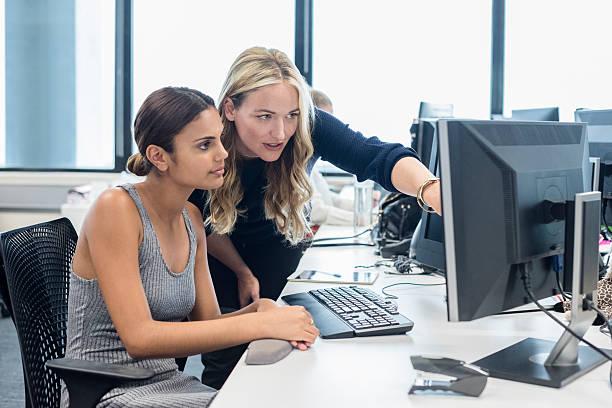 Businesswomen using desktop computer in modern office stock photo