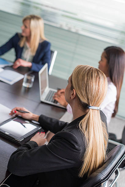 businesswomen using laptop and digital tablet on a meeting - directrice photos et images de collection