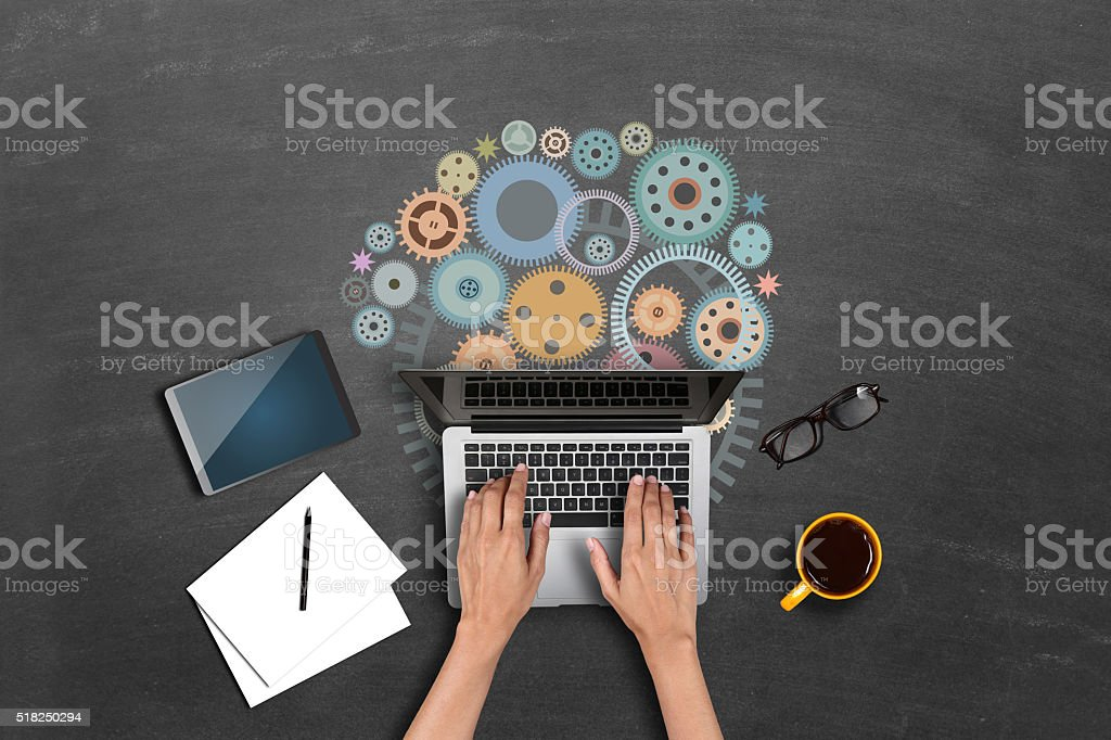Businesswomen using laptop with gears stock photo