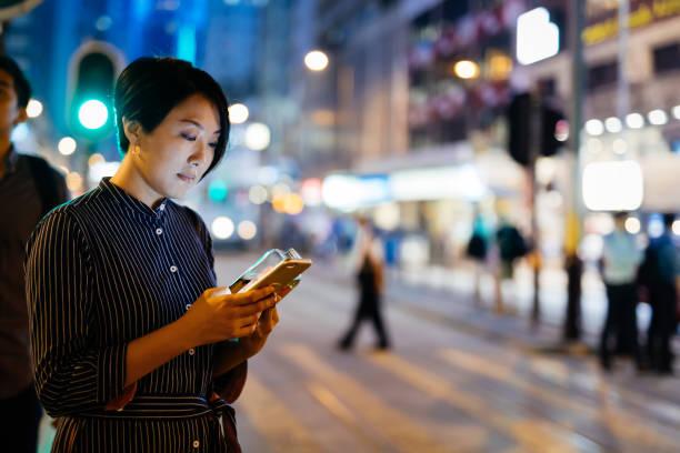 Businesswomen using smart phone at street stock photo