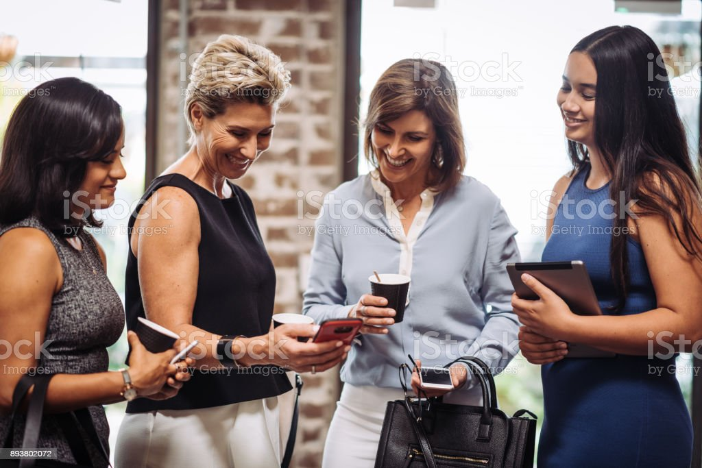 Geschäftsfrauen, die drahtlose Übertragung von Daten auf Smartphones mit – Foto