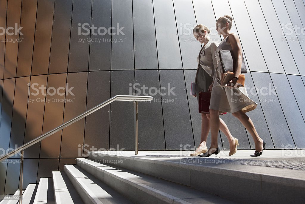 Businesswomen walking down steps outdoors stock photo