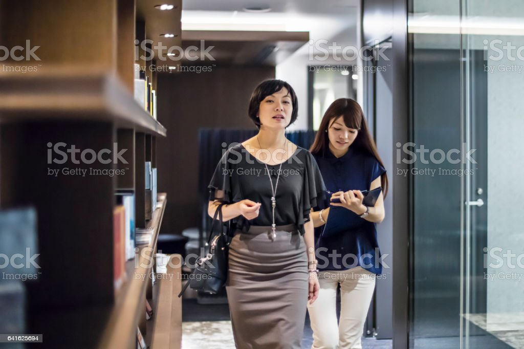 Businesswomen walking in office corridor stock photo