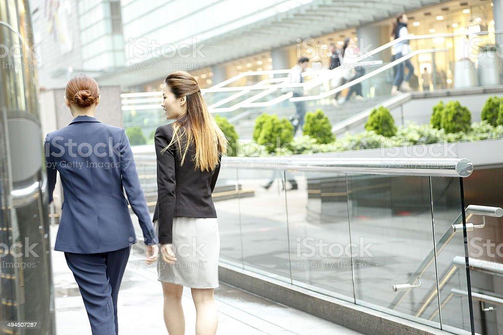 2 Businesswomen walking outside office towers stock photo