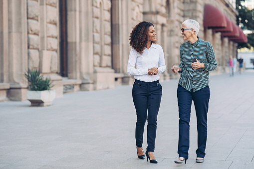 Two businesswomen walking together and talking outdoors in the city