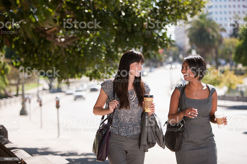 Businesswomen walking together outdoors stock photo