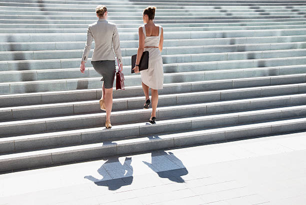 businesswomen walking up steps outdoors - staircase stock photos and pictures