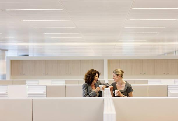 mujeres de negocio con café gossiping en cubículos de oficina - cotilleo fotografías e imágenes de stock