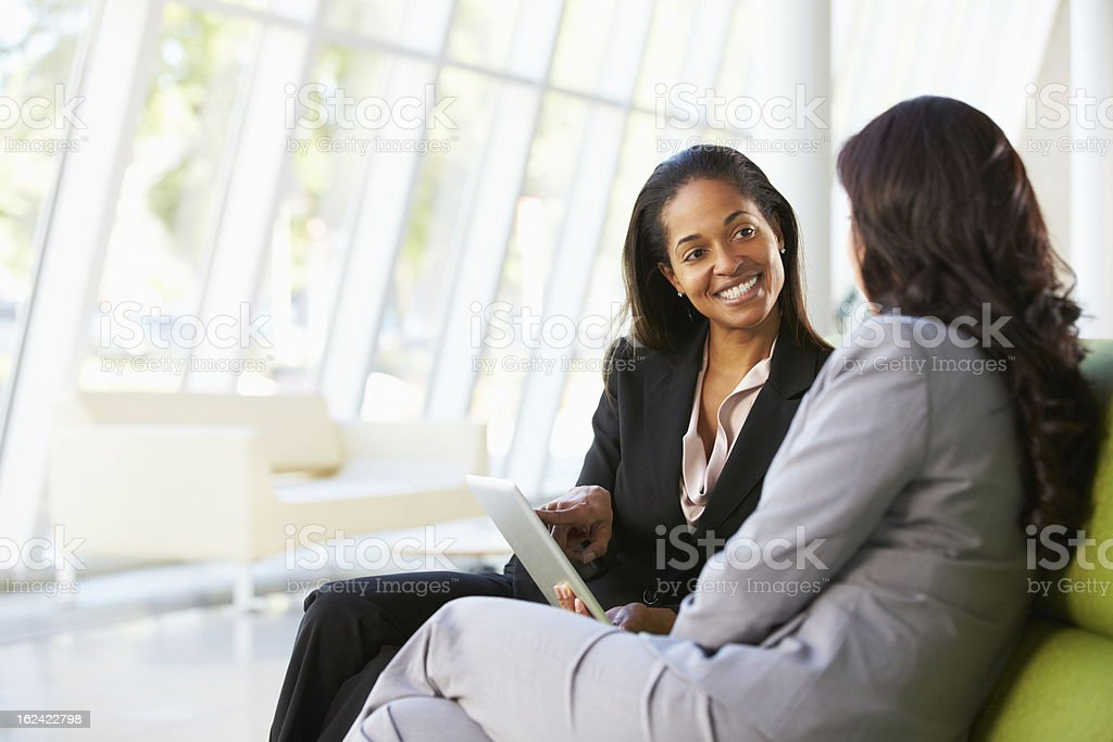 Businesswomen with digital tablet sit in an office stock photo