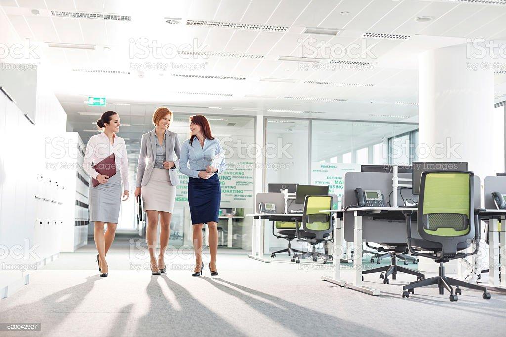 businesswomen with file folders walking in office royalty-free stock photo