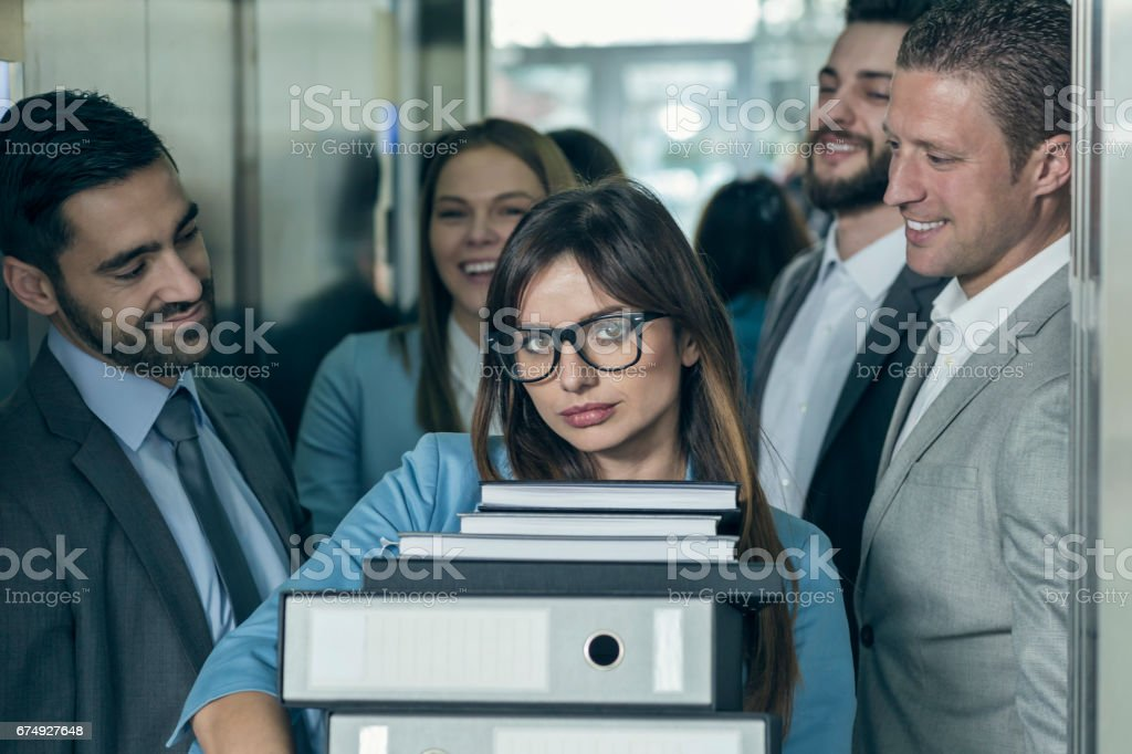 Businesswomen with hands full of documents leaving elevator stock photo