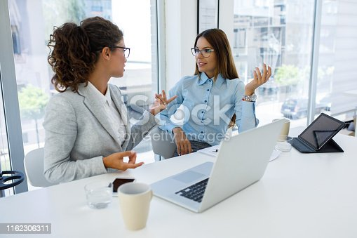 istock Businesswomen with laptop cooperating at work 1162306311