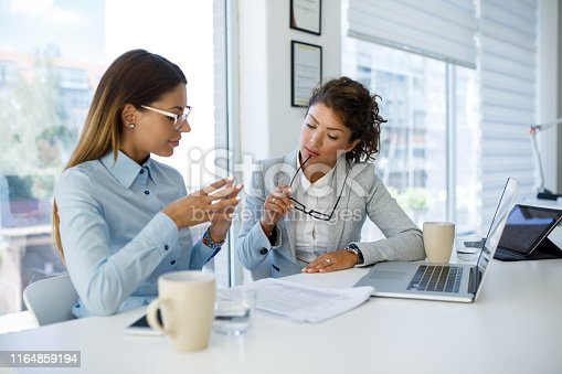istock Businesswomen with laptop cooperating at work 1164859194