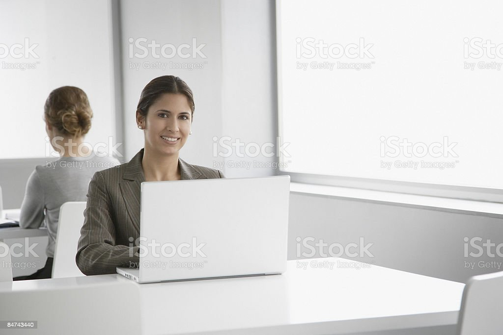 Businesswomen working on laptops in training room royalty-free stock photo