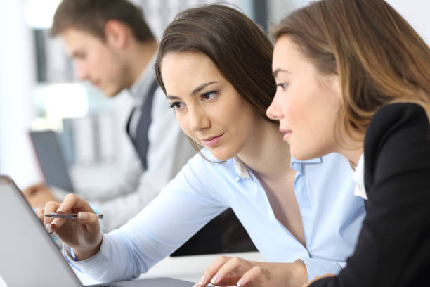 Businesswomen working on line together stock photo