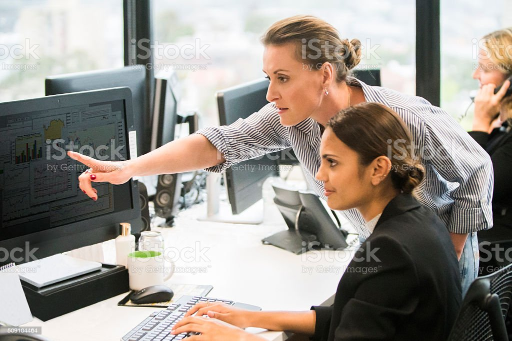 Businesswomen working together at computer workstation. stock photo